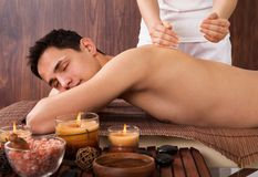Uomo rilassato che riceve massaggio della spalla in stazione termale immagine stock