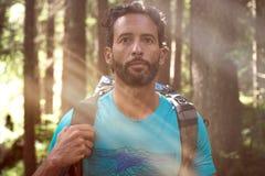 Uomo rilassato con il ritratto dello zaino sul percorso della traccia di escursione in legno della foresta durante il giorno sole Immagine Stock