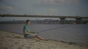 Uomo rilassato con pesca con la canna di filatura sul fiume archivi video