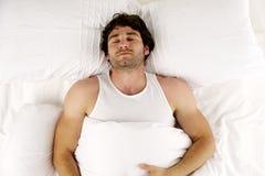 Uomo risieduto nel sonno bianco del letto Fotografie Stock Libere da Diritti
