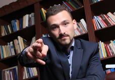 Uomo rispettabile accanto ad uno scaffale per libri Fotografie Stock