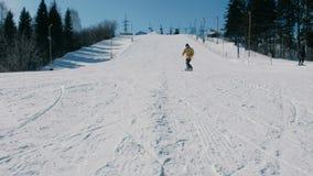 Uomo in rivestimento giallo che fa scorrere su uno snowboard dall'ascensore seguente del cielo di discesa della neve nel parco de video d archivio