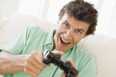 Uomo in salone che gioca i videogiochi Fotografia Stock Libera da Diritti
