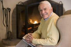 Uomo in salone con sorridere del giornale fotografie stock