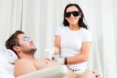 Uomo in salone cosmetico che riceve inceratura immagini stock libere da diritti