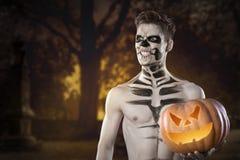 Uomo sanguinoso dello zombie con i cervelli fuori che tengono la zucca di Halloween orrore Halloween fotografia stock libera da diritti