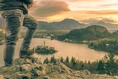 Uomo scalato sulle rocce ad alba Fotografie Stock