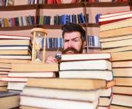 Uomo, scienziato che dà una occhiata dai libri Insegnante o studente con la barba che studia nella biblioteca Uomo sul fronte ser Fotografia Stock Libera da Diritti