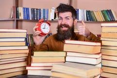 Uomo, scienziato che dà una occhiata dai mucchi dei libri con la sveglia Insegnante con la barba che studia nella biblioteca Conc Fotografia Stock Libera da Diritti