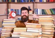 Uomo, scienziato che dà una occhiata dai mucchi dei libri con la sveglia Insegnante o studente con la barba che studia nella bibl Fotografia Stock