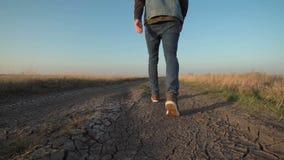 Uomo sconosciuto che si allontana giù una strada rurale archivi video