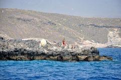 Uomo sconosciuto che sta sulla spiaggia dell'oceano e con il pesce del fermo della canna da pesca Fotografie Stock Libere da Diritti