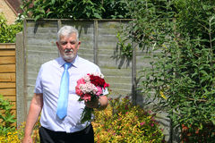 Uomo scuro con i fiori condoglianze Immagini Stock Libere da Diritti