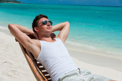 Uomo in sedia che prende il sole sulla spiaggia vicino all'oceano Immagine Stock