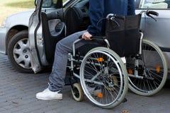 Uomo in sedia a rotelle accanto all'automobile Fotografie Stock