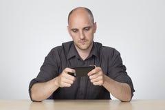 Uomo seduto allo scrittorio che gioca sul telefono fotografie stock