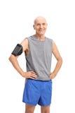 Uomo senior in abiti sportivi che ascolta la musica sul telefono Fotografia Stock