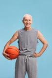 Uomo senior in abiti sportivi che tengono una pallacanestro fotografie stock