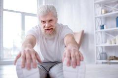 Uomo senior affascinante che posa mentre facendo allungamento Fotografia Stock