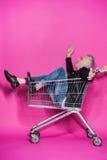 Uomo senior alla moda allegro divertendosi mentre sedendosi in carrello di compera Fotografia Stock Libera da Diritti