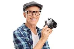 Uomo senior allegro che tiene una macchina fotografica Fotografia Stock