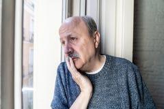 Uomo senior anziano infelice triste che soffre dalla perdita di memoria e da alzheimer che ritengono deprimenti e soli immagine stock libera da diritti