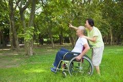 Uomo senior asiatico che si siede su una sedia a rotelle con la sua moglie immagine stock