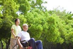 Uomo senior asiatico che si siede su una sedia a rotelle con la sua moglie immagini stock libere da diritti