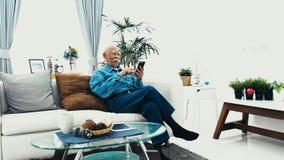Uomo senior asiatico con i baffi bianchi facendo uso del computer della compressa a casa, archivi video