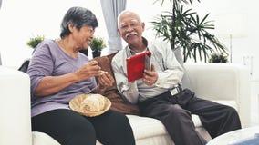 Uomo senior asiatico facendo uso del computer della compressa e del mestiere senior della mano della donna che tricotta lana a ca video d archivio