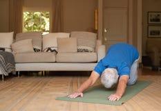Uomo senior attivo che si esercita su una stuoia di yoga a casa Immagine Stock Libera da Diritti