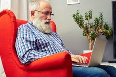Uomo senior barbuto che si siede con il computer portatile Fotografia Stock Libera da Diritti