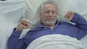Uomo senior bello che sveglia nel buon umore a casa dopo la notte calma piacevole video d archivio