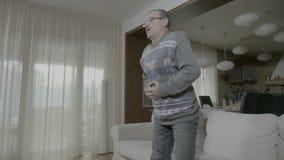 Uomo senior a casa che esprime sofferenza a causa del disagio di indigestione e dell'infiammazione dello stomaco che toccano la s video d archivio