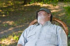 Uomo senior caucasico che dorme in una sedia di vimini nel parco di estate immagini stock
