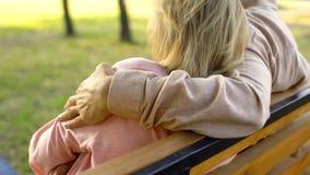 Uomo senior che abbraccia donna che si siede nel parco, relazioni romantiche, unità immagine stock