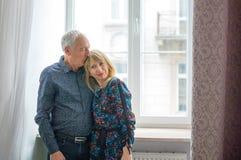 Uomo senior che abbraccia la sua giovane moglie bionda vicino alla finestra Donna che esamina la macchina fotografica Psicologia  fotografie stock
