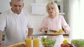 Uomo senior che aiuta moglie matura che mette pepe tagliato all'insalatiera video d archivio