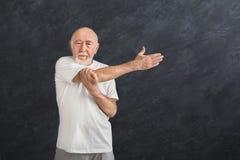 Uomo senior che allunga le mani all'interno Fotografia Stock
