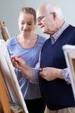 Uomo senior che assiste alla classe della pittura con l'insegnante fotografia stock