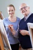 Uomo senior che assiste alla classe della pittura con l'insegnante fotografie stock libere da diritti