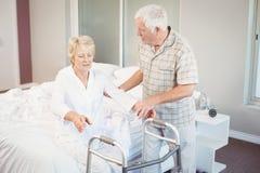 Uomo senior che assiste donna malata nell'alzarsi dal letto Immagini Stock Libere da Diritti