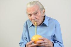 Uomo senior che beve il succo di pompelmo fresco Fotografia Stock Libera da Diritti