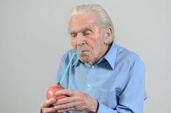 Uomo senior che beve il succo fresco del melograno Fotografie Stock Libere da Diritti