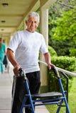 Uomo senior che cammina con il camminatore Fotografie Stock