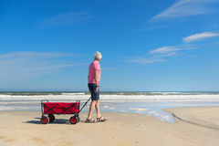 Uomo senior che cammina con il carretto alla spiaggia Fotografia Stock