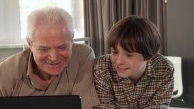 Uomo senior che chiede consiglio dal suo nipote immagine stock