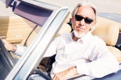 Uomo senior che conduce un'automobile classica convertibile Fotografia Stock
