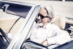 Uomo senior che conduce un'automobile classica convertibile Immagini Stock Libere da Diritti