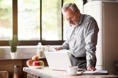 Uomo senior che controlla le sue carte in cucina a casa Fotografia Stock